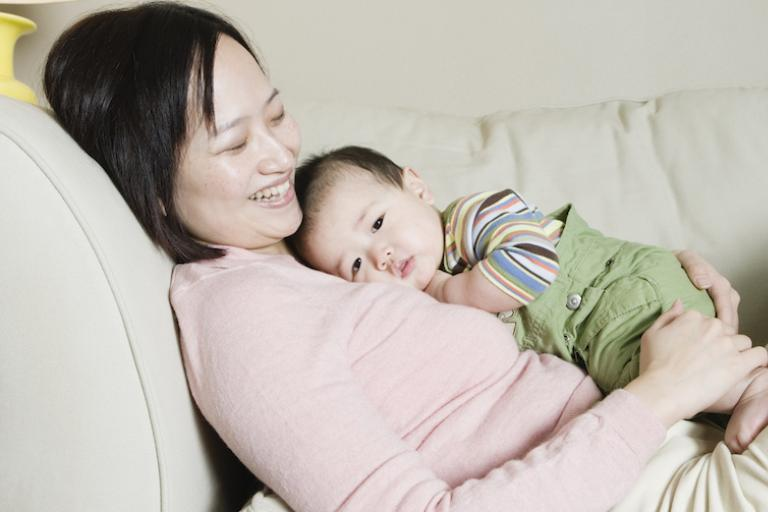 Woman and baby snuggling on couch