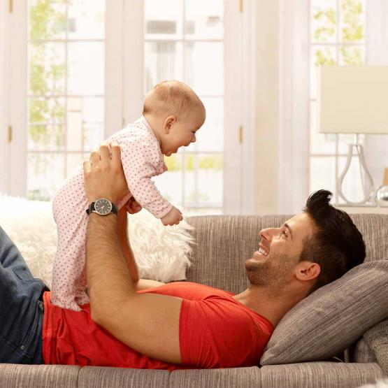 Father playing with baby on couch