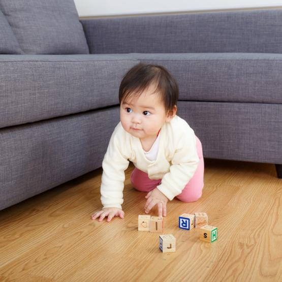 Baby crawling on floor with blocks