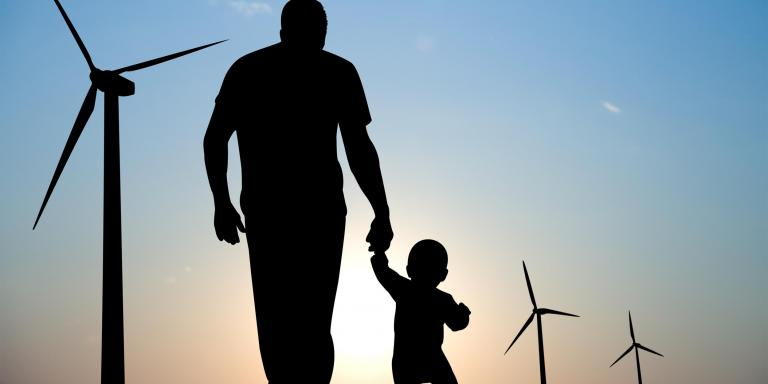 Father and son walking in front of windmills