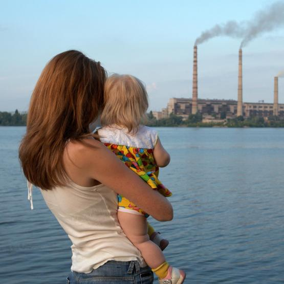 Mother and baby looking across river at smoke stacks